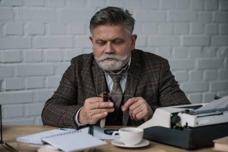 senior writer looking at watch while sitting at workplace
