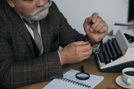 cropped shot of senior writer putting on his vintage watch at workplace