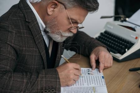 senior writer with pencil reading book at workplace