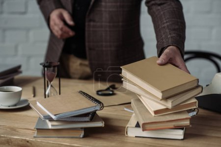 cropped shot of man taking stack of books from table