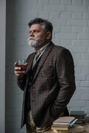 Photo for Senior man in tweed suit with glass of whiskey looking away - Royalty Free Image