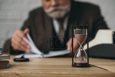 Photo pour Auteur principal travaillant avec sablier debout au premier plan - image libre de droit