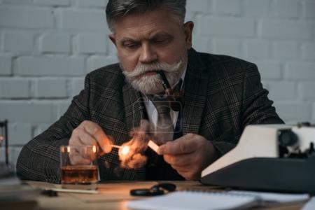 bearded senior writer with burning match smoking pipe at workplace