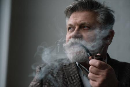 close-up portrait of bearded senior man smoking pipe