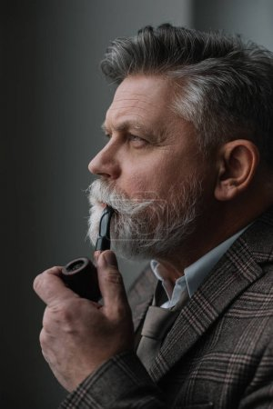 handsome senior man in tweed costume smoking pipe