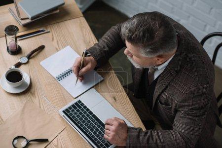 vue d'angle élevé de rédacteur principal de travail avec ordinateur portable et de prendre des notes dans le cahier
