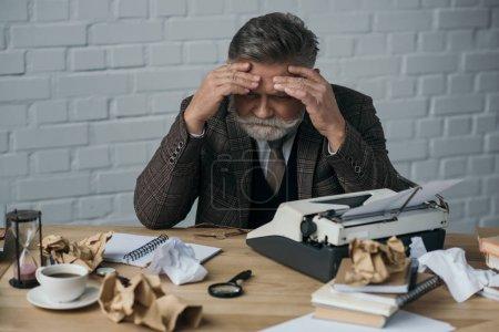 Photo pour Écrivain sénior déprimé assis à son lieu de travail désordonné et tenant la tête avec les mains - image libre de droit