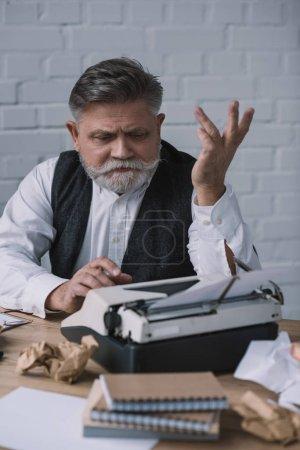 Photo pour Déprimé rédacteur principal essaie de travailler avec la machine à écrire au lieu de travail salissant - image libre de droit