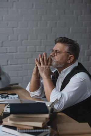 thoughtful senior man sitting at work desk with stacks of books