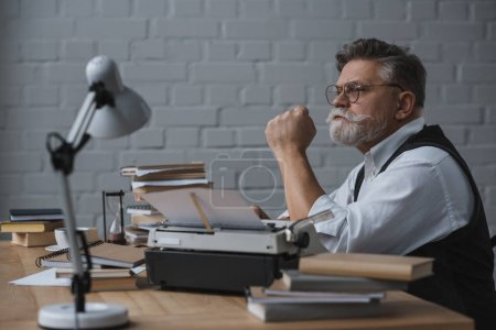 thoughtful senior writer sitting at workplace and looking away