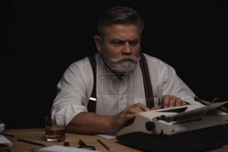 concentrated senior writer working with typewriter isolated on black