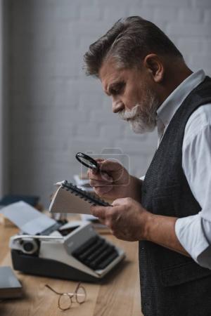 Foto de Principal escritor leyendo el manuscrito con lupa - Imagen libre de derechos
