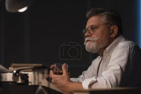 thoughtful senior writer sitting at workplace with glass of whiskey isolated on black