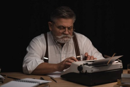 senior writer working with typing machine isolated on black