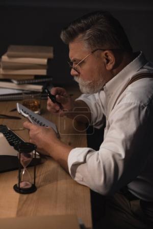 Foto de Concentra mayor escritor leyendo el manuscrito en el cuaderno con lupa - Imagen libre de derechos