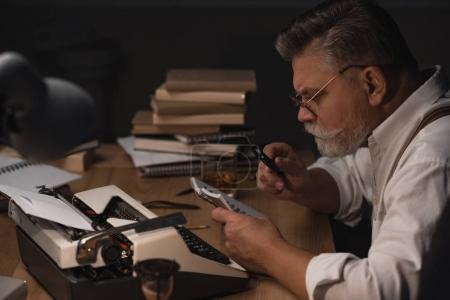 Foto de Principal escritor leyendo el manuscrito en el cuaderno con lupa - Imagen libre de derechos