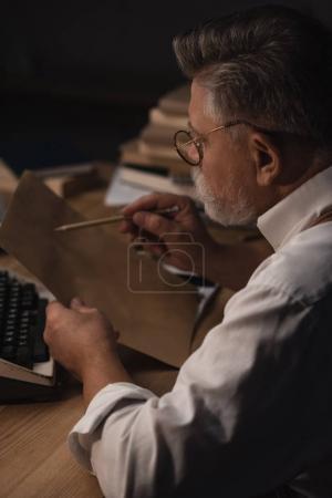 Foto de Concentrado senior escritor trabajando con manuscrito - Imagen libre de derechos