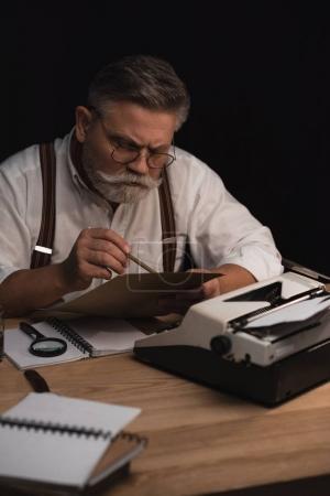 Foto de Escritor senior enfocado trabajando con manuscrito aislado en negro - Imagen libre de derechos
