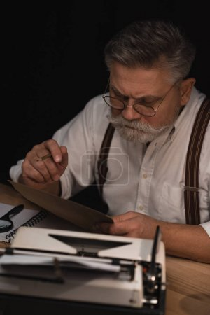 Photo pour Sérieux rédacteur senior travaillant avec manuscrit isolée sur fond noir - image libre de droit