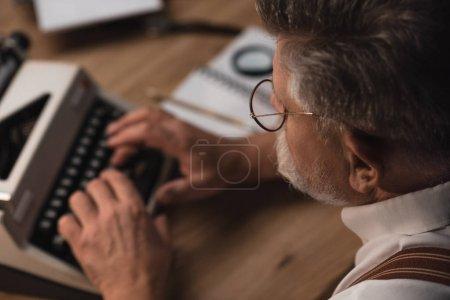 close-up shot of senior writer working with typewriter