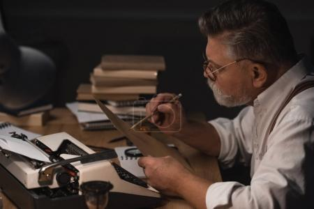 serious senior writer working with manuscript