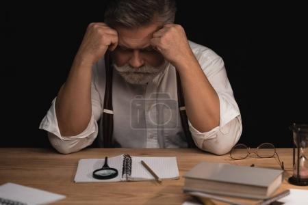 depressed senior writer sitting at workplace with blank manuscript