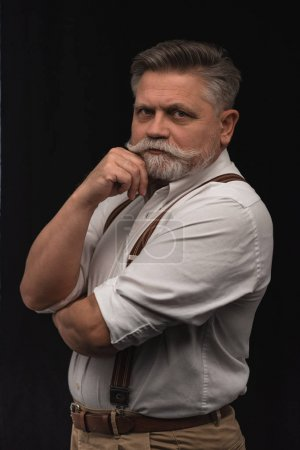 stylish senior man in white shirt with suspenders isolated on black