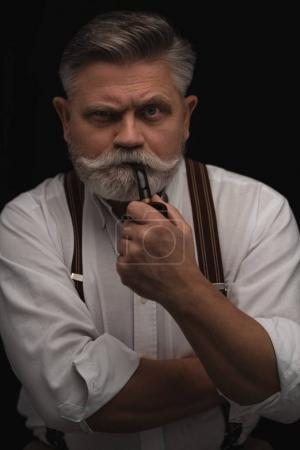mature man smoking pipe and looking at camera isolated on black