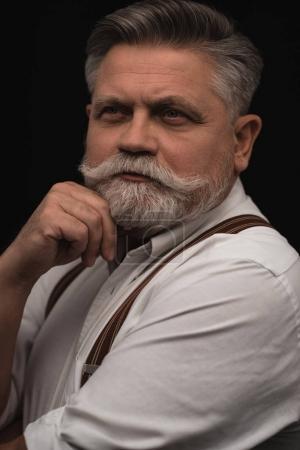 Photo pour Homme âgé réfléchi en chemise blanche avec des bretelles isolées sur noir - image libre de droit