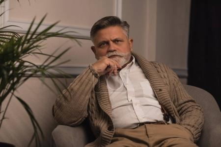 handsome senior man sitting in armchair and looking at camera
