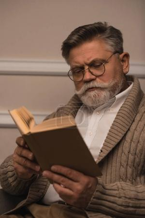 concentrated senior man in eyeglasses reading book