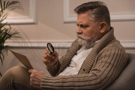 senior man reading letter with magnifying glass while sitting in armchair