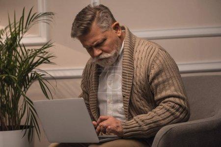 serious senior man using laptop while sitting in armchair