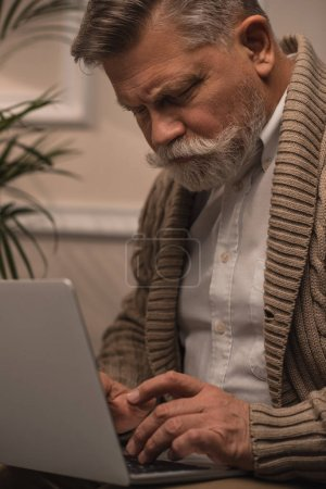 close-up shot of senior man using laptop