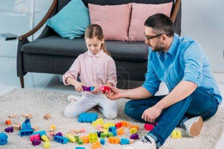 Foto de Poco de hija y padre jugando con coloridos bloques juntos en el piso en casa - Imagen libre de derechos