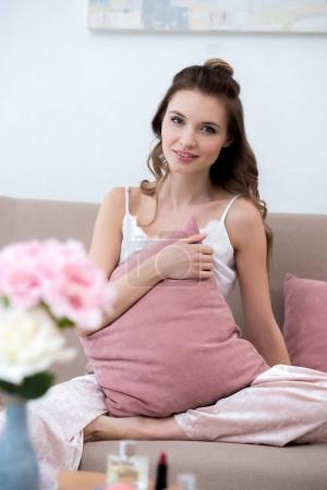 Photo for Beautiful girl in pajama holding pillow and smiling at camera at home - Royalty Free Image