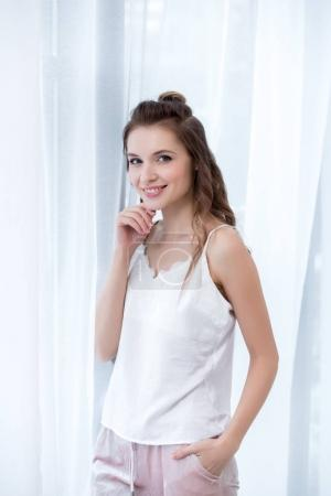 portrait of beautiful happy young woman in pajama smiling at camera
