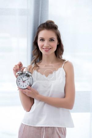 beautiful happy young woman in pajama holding alarm clock and smiling at camera