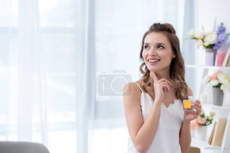 beautiful smiling young woman in lingerie holding bottle of perfume and looking away