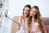 beautiful happy girlfriends taking selfie with smartphone at pajama party