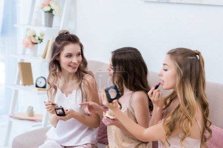 beautiful happy young women in pajamas applying makeup together