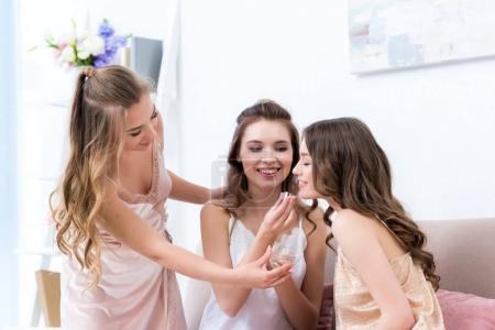 Photo pour Belles petites amies heureuses en pyjama sentant le parfum ensemble - image libre de droit