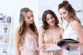 beautiful happy girlfriends in pajamas reading fashion magazine together