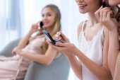 cropped shot of smiling young women in pajamas applying makeup while girlfriend talking by smartphone