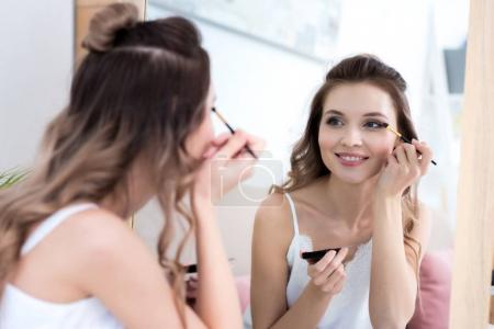 Photo pour Belle fille souriante regardant miroir et appliquant le maquillage - image libre de droit