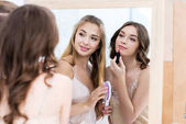 beautiful young women in pajamas applying makeup and looking at mirror