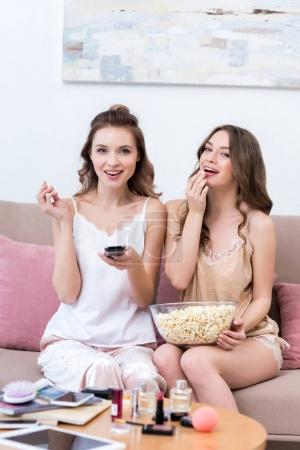 beautiful smiling young women eating popcorn and watching tv at pajama party