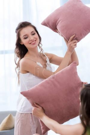 beautiful smiling girlfriends fighting with pillows at pajama party