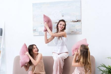 beautiful happy girlfriends in pajamas fighting with pillows at home