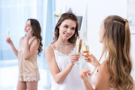 beautiful young women in pajamas drinking champagne while friend talking by smartphone